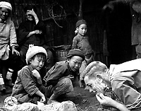 These two Chinese youngsters are fascinated by the sight of an American soldier shaving in the open.  Yunnan, China. June 1944. (Army)<br /> Exact Date Shot Unknown<br /> NARA FILE #:  111-SC-192535<br /> WAR &amp; CONFLICT BOOK #:  1265