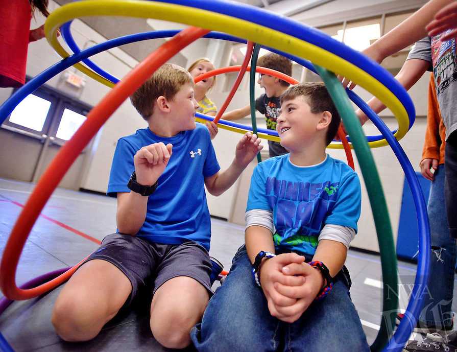 STAFF PHOTO BEN GOFF  @NWABenGoff -- 11/26/14 Mason Howell, left, and Austin Evans, both 8, get help from fellow campers building a ball of hula hoops around themselves while attending the School's Out Day Camp at the Rogers Activity Center on Wednesday Nov. 26, 2014.