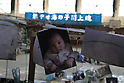 "The city of Natori became famous as the live broadcast of the tsunami tearing through it was seen around the world.  A month and a half later, rebuilding is still a distant thought.  Families struggle to sort through their heavily damaged homes.  In the Yuriage Elementary School gymnasium  photos recovered from the rubble  wait for their owners.  The banner reads, ""Burn with passion children of the sea: Yuriage spirit.""."