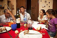 Italy. Lazio region. Capena. Dorel Andries (L), Catalin Busvioc (LC), his wife Luminita Nitita (RC) and their daughter Stefania Busvioc (R) enjoy a saturday night supper. They are all romanian citizens and have lived in Italy for the last years. Romanian immigration. Red tablecloth in flat's living room. Capena (until 1933 called Leprignano) is a town and comune in the province of Rome. 24.09.2011 © 2011 Didier Ruef