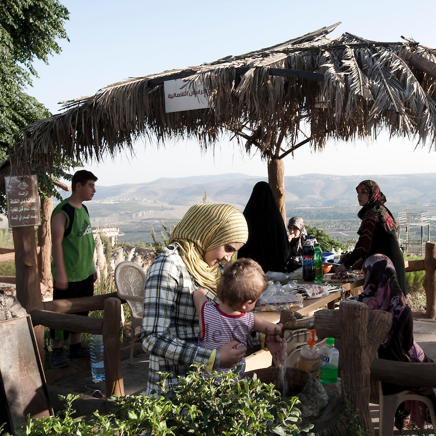 Lebanese family preparing a barbeque in the park. During his first state visit to Lebanon in October 2010  Iranian President Dr. Ahmadinejad went to Bint Jbeil, a village at Israel-Lebanon border. Its the place where fierce battles between Hizbullah and the Jewish Army were fought. In addition to praising the courage of the Lebanese nation against the powerful enemy supported by the US, France, Germany and Britain  Dr. ahmadinejad also performed the inauguration ceremony of the Iran Park at Maroun al-Ras border area where streets are named after the Iranian cities...The Iranian government has funded and designed a lush park near the site of the battle, on the mountainside directly overlooking Israel. In the parking, visitors can stand at an observation point beside an Iranian flag fluttering in the wind, and look directly down at the Israeli hamlets of Avivim and Yiron.