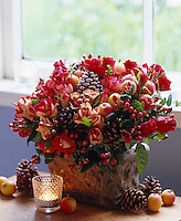 A winter inspired flower arrangement with apples, berries, roses and pine cones painted with glitter
