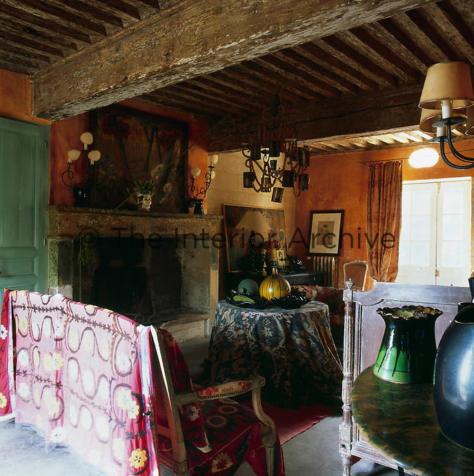 A rustic sitting room with a heavy beamed ceiling and a stone fireplace. The walls are painted a warm yellow ochre, reflecting the colours of the surrounding area of Provence and an antique sofa is draped with a pink pattern fabric.
