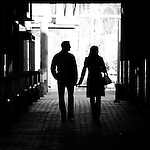 A silhouetted couple touching hands walking through a corridor