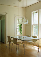 A contemporary dining area with an unusual pendant light