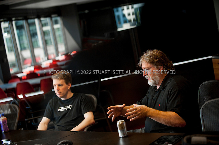 8/2/2012--Bellevue, WA, USA..Gabe Newell (right) is the co-founder and managing director of the video game development and online distribution company Valve, based in Bellevue, WA. Here he speaks with employee Robin Walker...The office is set up as a 'boss less' office that is fluid and non-hierarchical. Desks come with wheels so that they can be easily moved and reconfigured to create new work spaces for new projects. The desks can also be raised or lowered for comfort or to create a standing work space...©2012 Stuart Isett. All rights reserved.