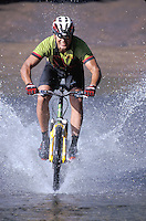 Hawaii, Kauai, mountain biker splashing through stream.