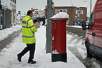 Postman collecting mail from local post office in snowy conditions.