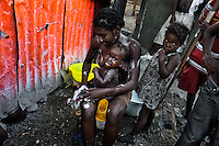 A Haitian girl bathes her baby outside a sheet-metal house in a shanty town close to La Saline market, Port-au-Prince, Haiti, 14 July 2008. Although Latin America (as a whole) is blessed with an abundance of fresh water, having 20% of global water resources in the the Amazon Basin and the highest annual rainfall of any region in the world, an estimated 50-70 million Latin Americans (one-tenth of the continent's population) lack access to safe water and 100 million people have no access to any safe sanitation. Complicated geographical conditions (mainly on the Pacific coast), unregulated industrialization (causing environmental pollution) and massive urban poverty, combined with deep social inequality, have caused a severe water supply shortage in many Latin American regions.