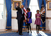 United States President Barack Obama waves after taking the oath of office as his daughters Malia and Sasha look on in the Blue Room of the White House in Washington, January 20, 2013. .Credit: Larry Downing / Pool via CNP