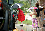 Florrie McCard, 7, waits paiently for her ride in the rain while after school at tommie Barfield elementary School Erik Kellar