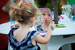 Olivia Mc Gurk, 4, of Los Altos admires herself in the mirror after getting her face painted during First Friday activities on the State Street Green in Los Altos.