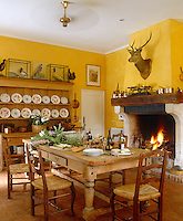 In this kitchen/dining room a roaring fire, bright yellow walls and antique copper pans exude warmth and comfort