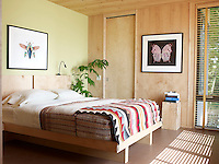 A pair of photographs by John Woolf hang in the master bedroom; the bed was built by Larry Ethier, the wall behind it is painted in Farrow & Ball's Churlish Green and the adjacent wall is mapel veneer