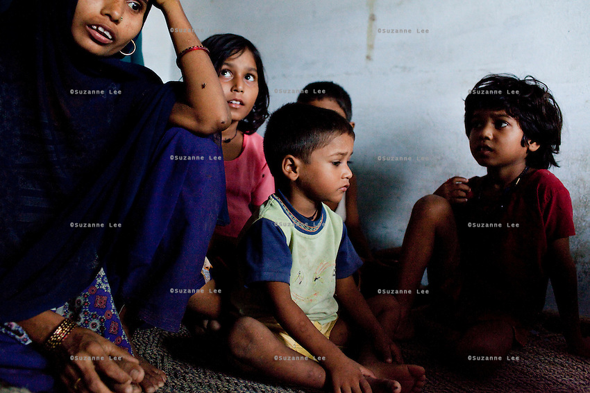 """Sitara (aged 35, extreme left), sits with her 7 children (5 daughters & 2 sons) as she breastfeeds her 8 month old baby girl in a village in Allahabad, Uttar Pradesh, India. """"I wish that I could stop getting pregnant but our religion says that children are a gift of God."""" Sitara is an illiterate muslim lady whose husband works as a vegetable vendor in the local village market. They have resisted all advises of permanent sterilization from the local village-level health workers. Children from left to right : Sufia (8), Asif (3), and Rani (7). Photo by Suzanne Lee / Panos London"""