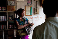 Rana Bahadur Magar (right), 24, attends to a customer in his pharmacy which he bought over 2 years ago in Gangate Village, Sathakhani Bidishi, Surkhet district, Western Nepal, on 30th June 2012. Monthly, Rana Bahadur Magar sells over 300 condoms and 1700 birth control pills and does about 10 injections of 3-month-long contraceptives which he is trained to do. The nearest district hospital is an hour's drive away. In Surkhet, StC partners with Safer Society, a local NGO which advocates for child rights and against child marriage.  Photo by Suzanne Lee for Save The Children UK
