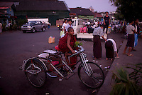 A novice monk waits on a trishaw at the docks in Rangoon (Yangon)