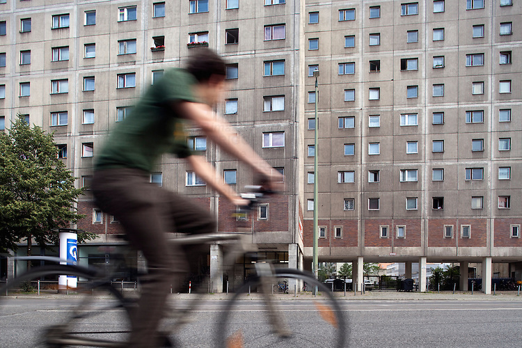 Cyclist in front of a typical Socialist building in the former East Berlin, Germany