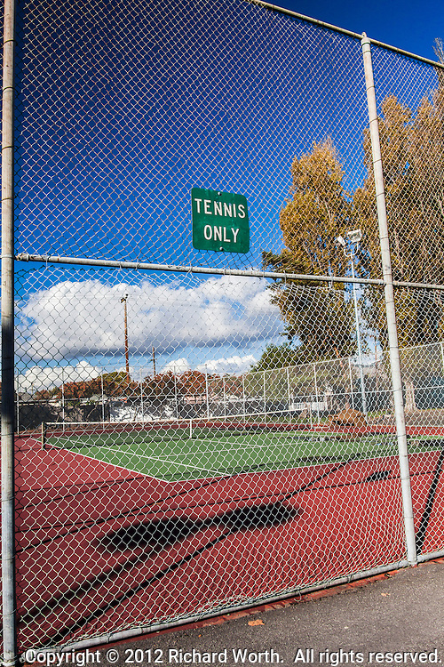 "The sign says, ""TENNIS ONLY"", but there is much more to see.  Shadows and lines, clouds and sky.  Trees and utility poles.  And that fence.  That chain link fence.  A virtual, visual sieve of steel diamonds.."