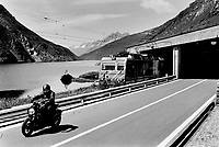 Switzerland. Canton Uri. Oberalp pass. A biker on the road. A regional train on tracks out of a tunnel. Fishermen on the Oberlap See. Oberalp Pass (Romansh: Alpsu or Cuolm d'Ursera, German: Oberalppass) (elevation 2044 m.) is a high mountain pass in the Swiss Alps connecting the cantons of Graubünden and Uri. 30.07.2016  © 2016 Didier Ruef