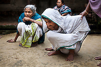 """(L-R: (blue) Saraswati Saha, 84; unnamed; and (white) Kamla Das, 90) Three elderly women who were the original refugees of The Partition recall being brought to Cooper's Camp on trains and trucks as they gather outside their homes in Cooper's Camp, Nadia district, Ranaghat, North 24 Parganas, West Bengal, India, on 19th January, 2012. """"The government will neither eat us nor spit us out."""" says Kamla Das. """"They dropped us off here (in 1947) and I'm still here!"""" Over 60 years after the bloody creation of Bangladesh in 1947, refugees who fled what was then known as West Pakistan to India still live as refugees, raising their children as refugees, and standing in line for government handouts..Photo by Suzanne Lee for The National (online byline: Photo by Szu for The National)"""