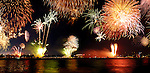 Panoramic scenery of colorful firework display over a city waterfront