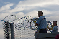 Prison guards finish the last few meters of the fence on the border between Serbia and Hungary near Roszke (about 174 km South of capital city Budapest), Hungary on September 14, 2015. ATTILA VOLGYI