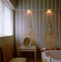 Trompe l'oeil busts and drapes feature in this blue and white guest bathroom