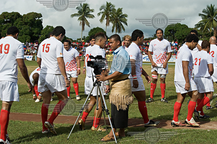 Teams enter the field for the rugby match between an invited World 15 team and Ikaletahi, the home Tongan national team. The home team won 60 - 26. The event was part of the national celebrations spanning five days to mark the coronation of King George Tupou V.