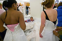 "Linda Penceal (C) watches her daughter and bride-to-be Moshe Penceal (L) try on discounted wedding dresses during the annual ""Running of the Brides"", a a first-come-first-served bridal gown sale, at the Filene's Basement store in New York City, USA, 3 March 2006."