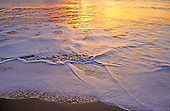 Beautiful close-up of foam and water on the shoreline of Hanakanaia Beach on Kahoolawe, reflecting the golden sunset.