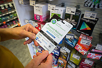 A shopper chooses a Vanilla brand prepaid card in a store in New York on Friday, August 1, 2014. Federal law enforcement is concerned about the fraudulent schemes being perpetrated on consumers using prepaid money cards as well as money laundering by criminals. Consumers are expected to put approximately $80 billion on prepaid debit cards this year which is twice the amount loaded in 2010. (© Richard B. Levine)