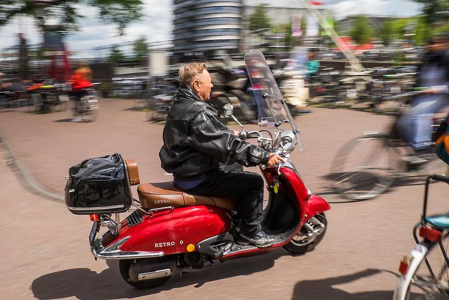 Nederland, Amsterdam, 30 mei 2015<br /> Snorscooter in het centrum van de stad.  Scooters stoten veel fijn stof uit en zijn enorm ongezond voor de stadsbewoners. De luchtkwaliteit wordt ernstig aangetast door scooters en bromfietsen of snorfietsn. Scooters irriteren veel verkeersdeelnemers omdat ze zich niet aan de verkeersregels houden.<br />  <br /> Foto: Michiel Wijnbergh
