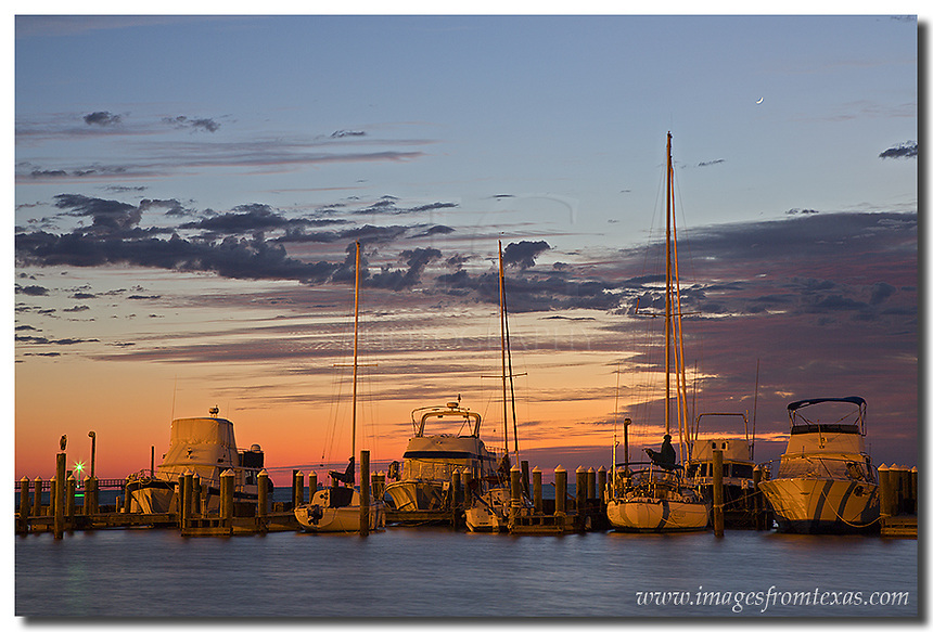 The sky was beginning to show some color but the sunrise was still ways away. The harbor at Rockport, Texas, was failry calm in its protected cover. The seagull, cranes, and other feather friends were waiting for the shrimp boats to arrive, as well. This Texas image of the gulf coast captures the early morning hours when all was calm.