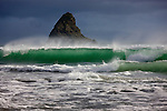 An emerald colored wave comes crashing to the beach with a pancake rock behind, Punakaiki, New Zealand.