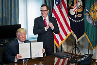 US President Donald J. Trump (L), with Secretary of Treasury Steven Mnuchin (R), participates in a financial services Executive Order signing ceremony in the US Treasury Department building in Washington, DC, USA, 21 April 2017. President Trump is making his first visit to the Treasury Department for a memorandum signing ceremony with Secretary Mnuchin.<br /> Credit: Shawn Thew / Pool via CNP /MediaPunch