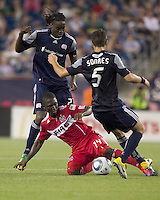 Chicago Fire midfielder Patrick Nyarko (14) fails to successfully dribble against two New England Revolution defenders, including New England Revolution midfielder Shalrie Joseph (21). In a Major League Soccer (MLS) match, the New England Revolution tied the Chicago Fire, 1-1, at Gillette Stadium on June 18, 2011.