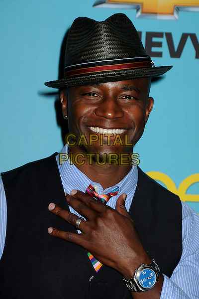 """TAYE DIGGS .Fox's """"Glee"""" Spring Premiere Soiree held at Bar Marmont, West Hollywood, California, USA, .12th April 2010..portrait headshot hat red blue shirt tie striped waistcoat plaid checked check tartan hand smiling wrist watch .CAP/ADM/BP.©Byron Purvis/AdMedia/Capital Pictures."""