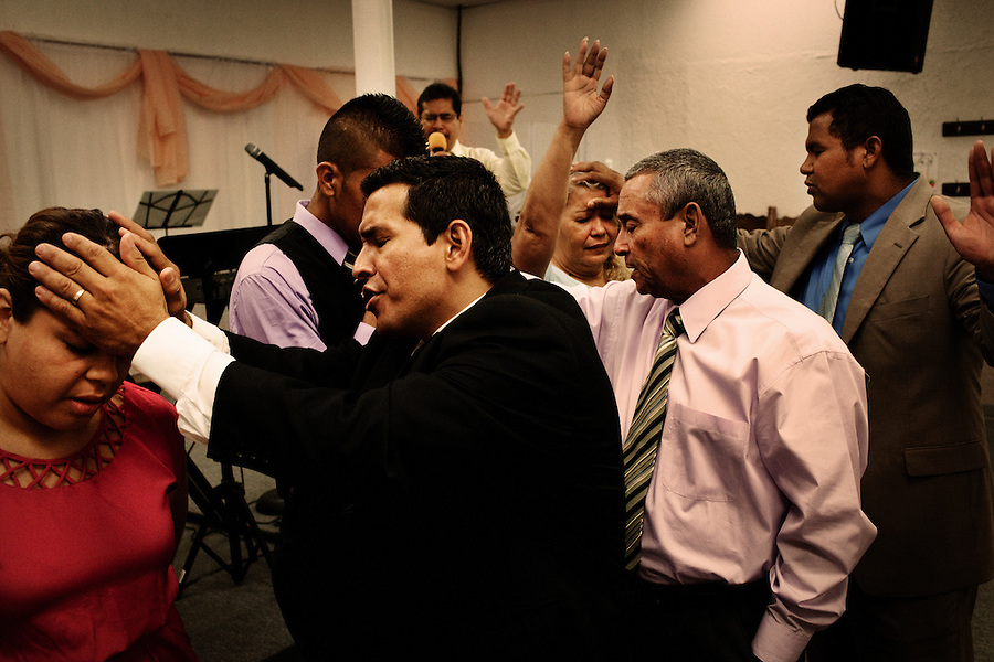 Central Falls, Rhode Island, July 15, 2012 - Pastor Narciso Romero prays over one of his congragants at Iglesia Pentecostal Unida. Churches and religious organizations are helping to fill some gaps and keeping the community together. Iglesia Pentecostal Unida hosts events several nights each week for its congregation. <br /> <br /> Central Falls, a city of about 19,000 just north of Providence, is both the smallest and most densely populated city in Rhode Island. It also has the distinction of being one of a handful in the US to file for bankruptcy. The city&rsquo;s economy began to decline in the 1970s with the departure of manufacturers, particularly in the textile sector where 11 plants closed between 1997 through 2007. By the 1990&rsquo;s the state was eventually forced to take over the city&rsquo;s schools system, including 100 percent of its funding. The Great Recession in 2008 added further pain when the state was forced to drastically cut aid to cities and towns. <br /> <br /> Central Falls problem was that spending continued unabated even though its revenues were down sharply. For years its government failed to contribute to its police and firefighters&rsquo; pension fund, eventually leaving the fund broke. With an $80 million unfunded pension &ndash; which is 5 times that of the city&rsquo;s $17 million budget - and obligation to cover health benefits,  it had no option but to file for Chapter 9 protection. <br /> <br /> The city&rsquo;s downfall mirrors patterns found in many of the other municipalities near or in Chapter 9, including Stockton, Mammoth Lakes and San Bernardino, CA as well as Harrisburg, PA and Jefferson County, AL, where spending far outpaced shrinking revenues.