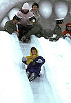 Festival goers slide down an ice slide at the Japanese Self Defense Force Base at Makomanai. Nearly two million visitors pour into Sapporo every February to see over 200 ice and snow sculptures..These are not traditional Frosty the Snowmen, but huge carved and chiseled Samurai Warriors, Buddhists gods, historical heroes of fairy tales and Walt Disney characters. Some stand as big as buildings. Chiseled out of tons of packed snow, the sculptures are the pride and job of the residents of Sapporo, Japan, who hosts the world famous Ice and Snow Sculpture Festival for five days in early February.Themes of the sculptures are picked from Kabuki stages, historical characters or fairy tales. (Jim Bryant Photo).....