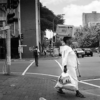 A woman with a microwave oven balanced on her head crosses the road at the junction of Nugget and Wolmarans Streets in Hillbrow.
