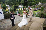"Portmeirion, in North Wales, is a resort, where no one has ever lived. A self-taught Welsh architect named Sir Clough Williams-Ellis built it out of architectural salvage between the 1920s and 1970s, loosely based on his memories of trips to Portofino. Including a pagoda-shaped Chinoiserie gazebo, some Gothic obelisks, eucalyptus groves, a crenellated castle, a Mediterranean bell tower, a Jacobean town hall, and an Art Deco cylindrical watchtower. He kept improving Portmeirion until his death in 1978, age 94. It faces an estuary where at low tide one can walk across the sands and look out to sea. At high tide, the sea is lapping onto the shores. Every building in the village is either a shop, restaurant, hotel or self-catering accomodation. The village is booked out at high season, with numerous wedding receptions at the weekends. Very popular amongst the English and Welsh holidaymakers. Many who return to the same abode season after season. Hundreds of tourists visit every day, walking around the ornamental gardens, cobblestone paths, and shopping, eating ice-creams, or walking along the woodland and coastal paths, amongst a colourful assortment of hydrangea, rhododendrons, tree ferns and redwoods. The resort boasts two high class hotels, a la carte menus, a swimming pool, a lifesize concrete boat, topiary, pools and wishing wells. The creator describes the resort as ""a home for fallen buildings,"" and its ragged skyline and playful narrow passageways which were meant to provide ""more fun for more people."" It does just that.///Wedding photography taking place at the Baroque Renaissance colonnade and patio with steps leading down to ornamental gardens."