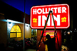 Nano Lopez removes a ladder after renovating signage at the Hollister Inn on San Felipe Road near the edge of town in Hollister, Calif. <br />
