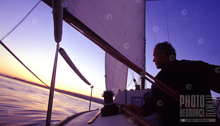 Man sailing at sunset in smooth seas