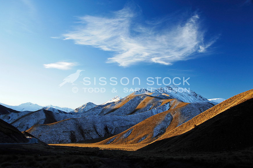 Late afternoon sun casts shadows across snow dusted hills in the the Lindis Pass, Central Otago, South Island, New Zealand - stock photo, canvas, fine art print