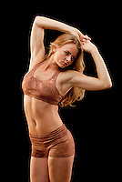 Young muscular woman facing forward, hands over head