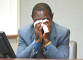 James Allen Gray Jr., president and publisher of &quot;Bessemer Daily News&quot; in Bessemer, Alabama, wipes his face as he identifies Lee Boyd Malvo during testimony in the trial of sniper suspect John Allen Muhammad at the Virginia Beach Circuit Court in Virginia Beach, Virginia on October 22, 2003.  Gray chased a suspect in a shooting at an Alabama liquor store in 2002. <br /> Credit: Davis Turner - Pool via CNP