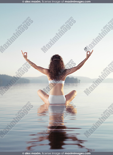 Artistic concept of a woman meditating with a butterfly on her hand. Practicing meditation on a floating platform in calm water of a lake in early morning during sunrise. Yoga meditation. Rear view. Muskoka, Ontario, Canada.