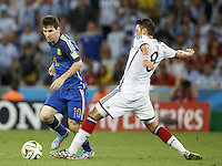 Lionel Messi of Argentina takes on Mesut Ozil of Germany