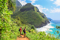 Two hikers on the Kalalau Trail near Hanakapi'ai Beach admire Kaua'i's Na Pali (or Napali) coastline.